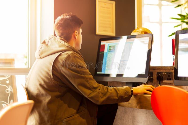 Junger Studentenmann, der an einem Computer studiert in der Bibliothek arbeitet lizenzfreie stockfotos