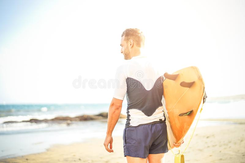 Junger Surfer, der sein Surfbrett sucht die Wellen nach dem Surfen - Stellung des gut aussehenden Mannes auf dem Strand am Sonnen lizenzfreie stockbilder