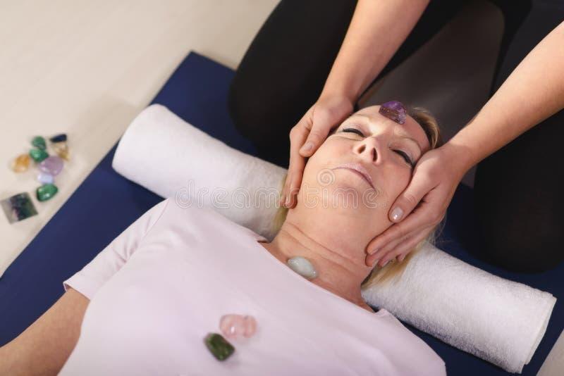 Junger Therapeut, der Kristalle auf weiblichem Kunden für reiki Th anordnet stockbild