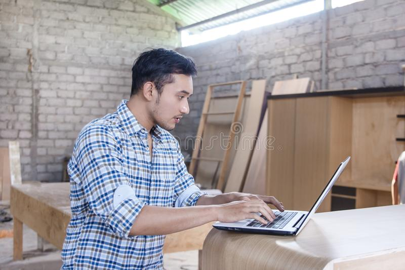 Junger Tischler, der an seinem Laptop arbeitet lizenzfreie stockfotos