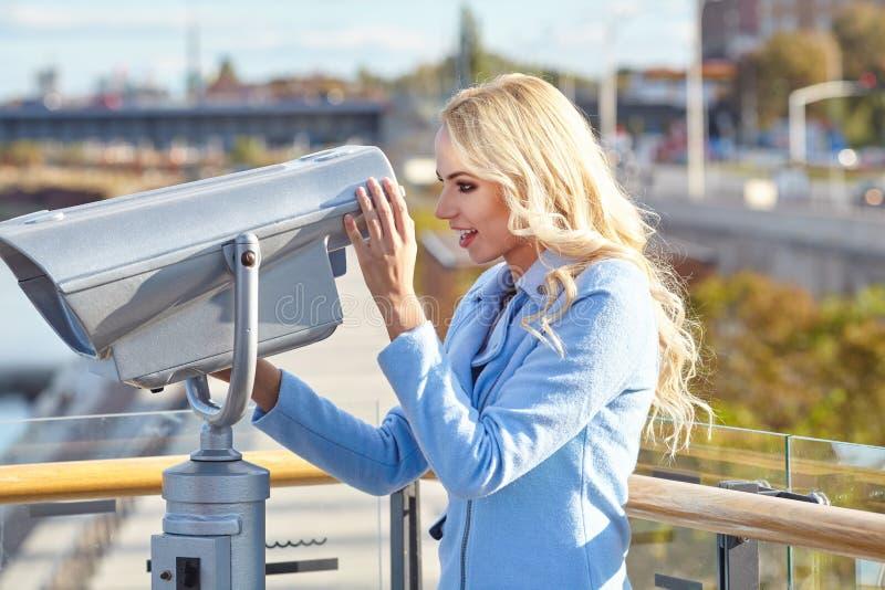 Junger Tourist, der Teleskopturmaussichtsplattform I verwendet lizenzfreie stockfotografie