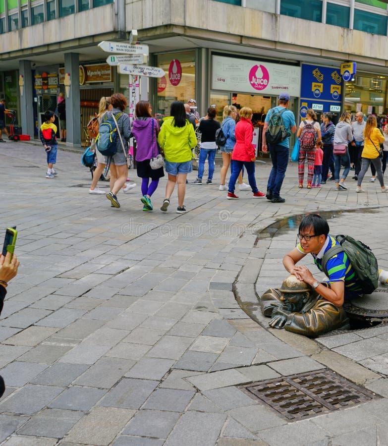 Junger Tourist erhält Foto gemacht auf Abwasserkanalskulptur lizenzfreie stockfotos