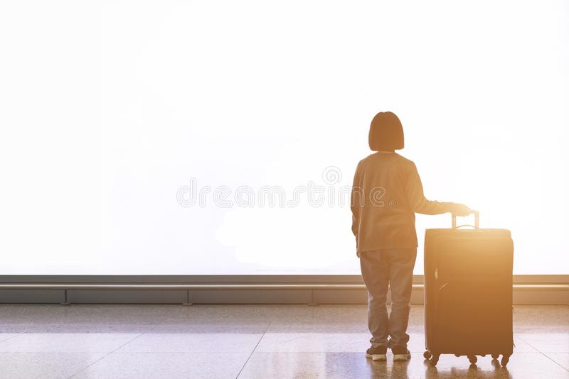 Junger Tourist mit dem Gepäck, das vor großer weißer heller Anschlagtafel am Flughafen steht lizenzfreies stockbild