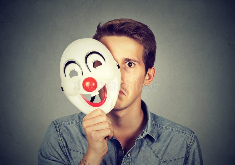 Junger trauriger Mann, der hinter glücklicher Clownmaske sich versteckt lizenzfreie stockfotografie