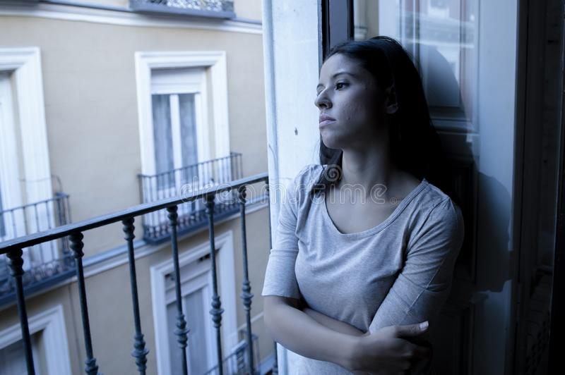 Junger trauriger und hoffnungsloser lateinischer Balkon der Frau zu Hause, der zerstörte und niedergedrückte leidende Krise glaub lizenzfreies stockbild