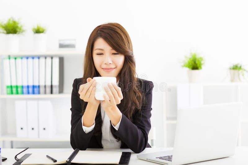 junger trinkender Kaffee der Geschäftsfrau im Büro lizenzfreie stockbilder