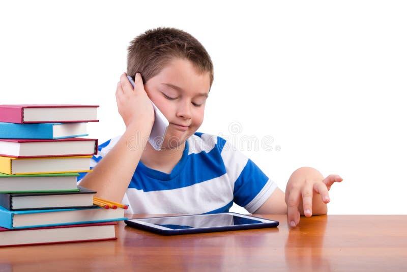 Junger Tweenjunge, der an einem Handy plaudert stockfotografie