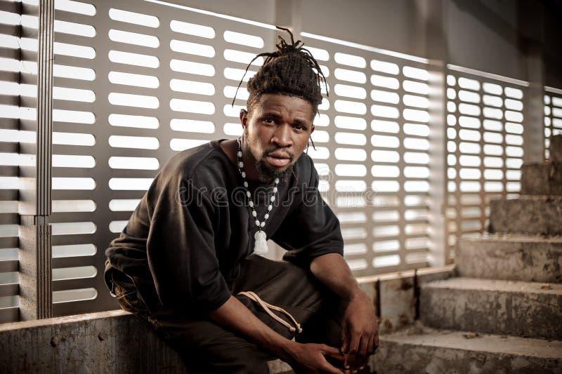 Junger und attraktiver afroer-amerikanisch Mann, der nahe dem Fenster sitzt lizenzfreie stockfotografie