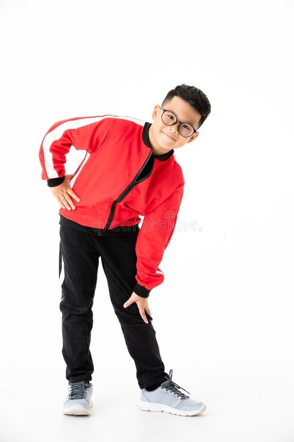 Junger und hübscher junger asiatischer Junge in den roten und schwarzen Stoffen stehen lizenzfreie stockbilder