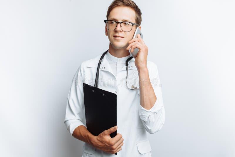 Junger und hübscher Doktor, der in der Hand am Telefon mit Patienten, Interniertstudent mit Ordner, weißer Hintergrund, für adver lizenzfreie stockfotografie