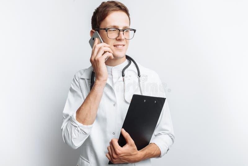 Junger und hübscher Doktor, der in der Hand am Telefon mit Patienten, Interniertstudent mit Ordner, weißer Hintergrund, für adver stockbild