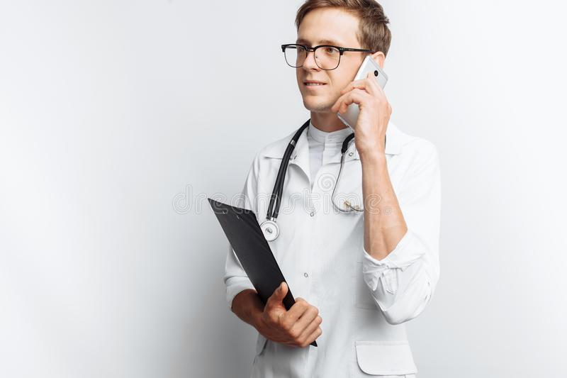 Junger und hübscher Doktor, der in der Hand am Telefon mit Patienten, Interniertstudent mit Ordner, weißer Hintergrund, für adver lizenzfreies stockfoto