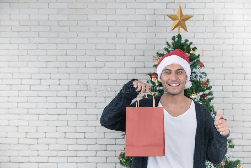 Junger und hübscher kaukasischer Mann, der rote Einkaufstasche und Th hält stockfotografie