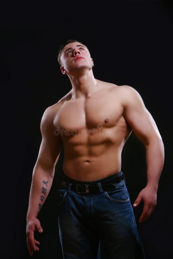 Junger und muskulöser Mann auf Schwarzem stockfotos