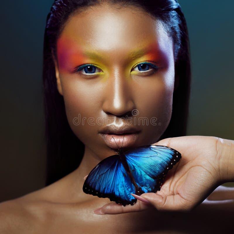 Junger und schöner schwarzer vorbildlicher exotischer Blick mit hellem blauem Schmetterling lizenzfreies stockfoto
