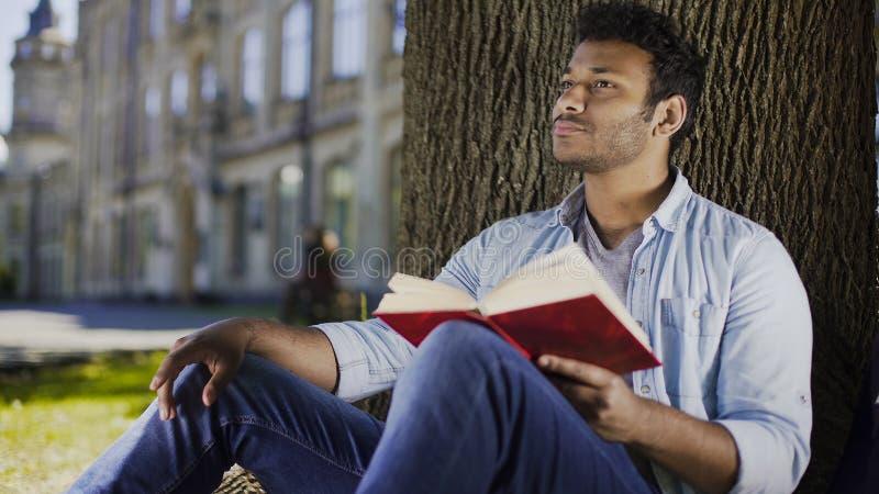 Junger unter Baumlesebuch sitzender und denkender Mann, Fiktionsliteratur lizenzfreies stockbild