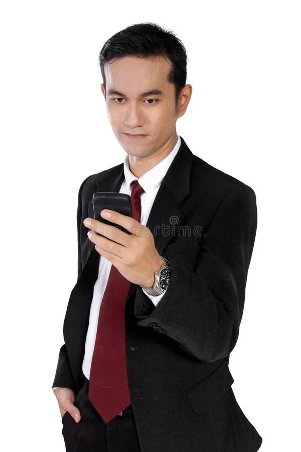 Junger Unternehmer, der an der E-Mail am Telefon, lokalisiert auf Whit überprüft lizenzfreies stockfoto