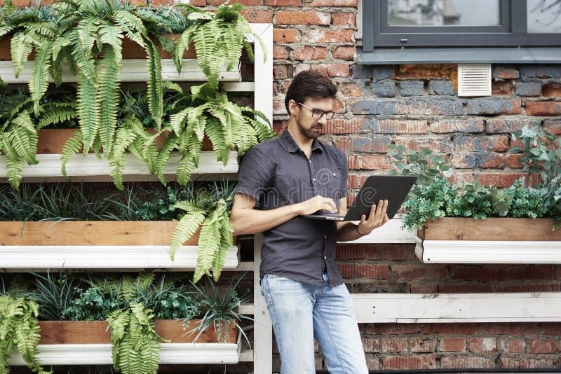 Junger Unternehmer, der draußen unter Verwendung des modernen Laptops arbeitet Stehende nahe Backsteinmauer, Anlagen, eco Büro Er lizenzfreies stockbild