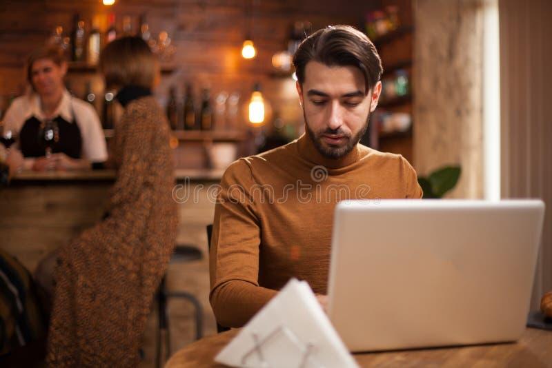 Junger Unternehmer, der an seinem Laptop in einer Kaffeestube arbeitet stockbilder