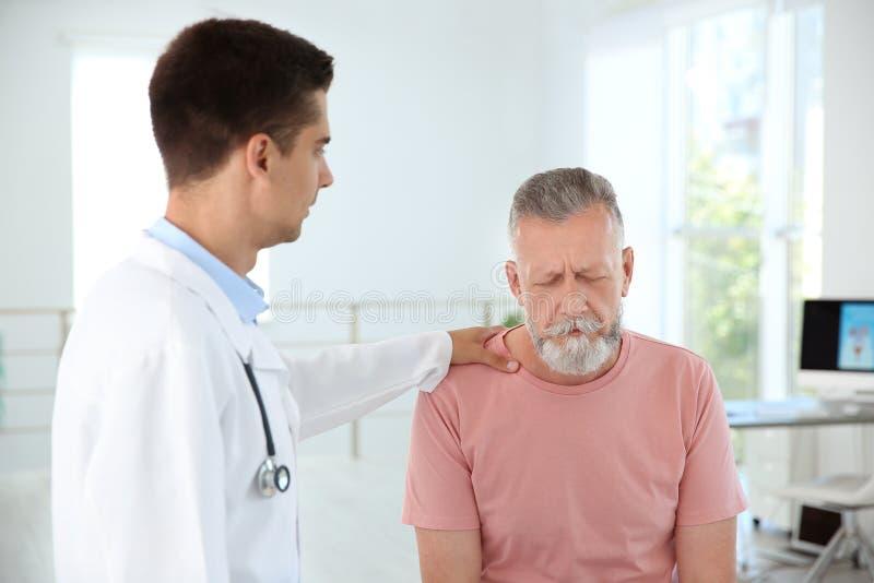 Junger Urologe, der umgekippten Patienten tröstet lizenzfreies stockfoto