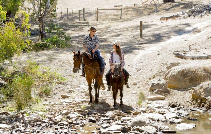Junger Vater als Pferdelehrer der Tochter des jungen jugendlich, die tragenden Cowgirlhut des kleinen Ponys reitet stockfotos
