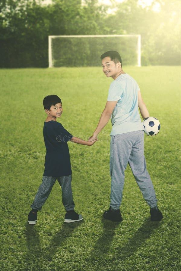 Junger Vater, der einen Ball mit seinem Sohn trägt stockfotografie