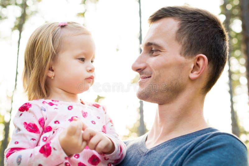 Junger Vater, der nette Kleinkindmädchentochter in seinem Arm hält, sie lächelt und betrachtet lizenzfreie stockfotos