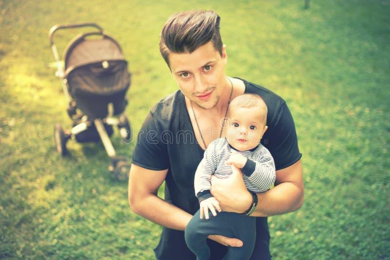 Junger Vater, der neugeboren, 3 Monate alte Sohn hält und küsst Weinleseeffekt, getontes Bild, instagram lizenzfreie stockfotografie