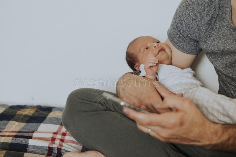 Junger Vater, der sein Baby hält lizenzfreie stockbilder