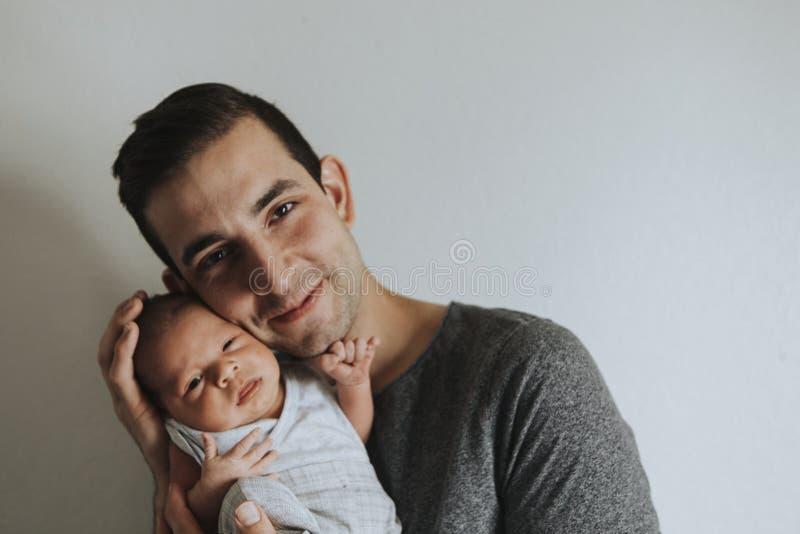 Junger Vater, der sein Baby hält lizenzfreies stockfoto