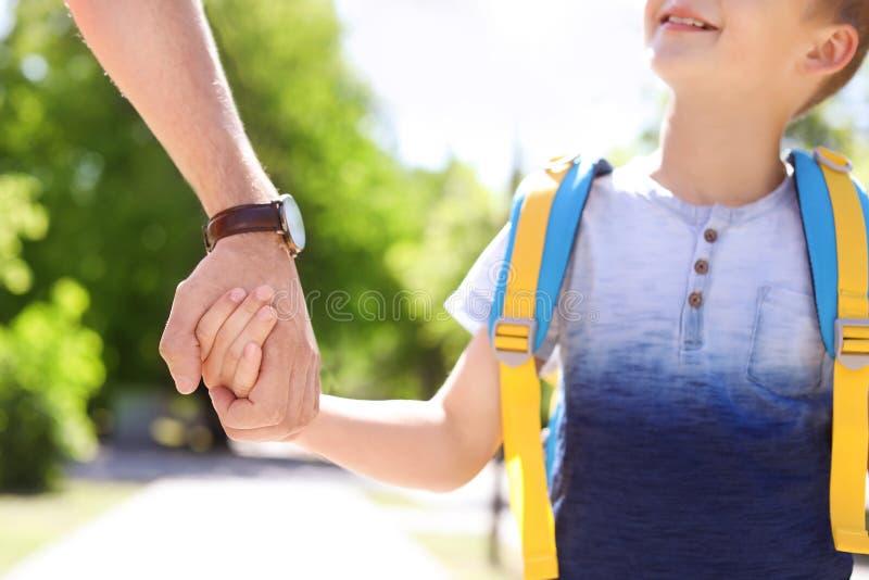 Junger Vater, der sein Kind zur Schule nimmt lizenzfreie stockfotos
