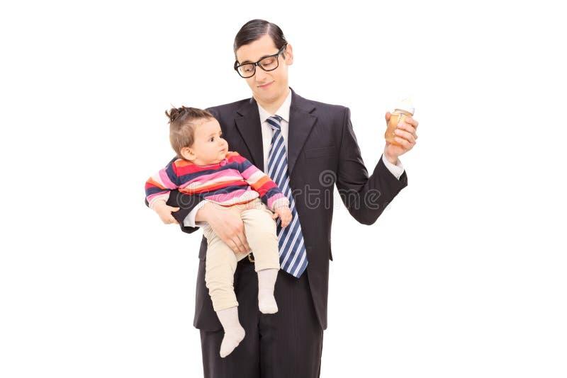 Junger Vater, der seine Tochter und Flasche Saft hält lizenzfreie stockfotos
