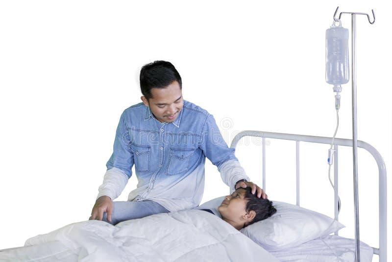 Junger Vater, der seinen kranken Sohn auf Studio besucht stockbilder