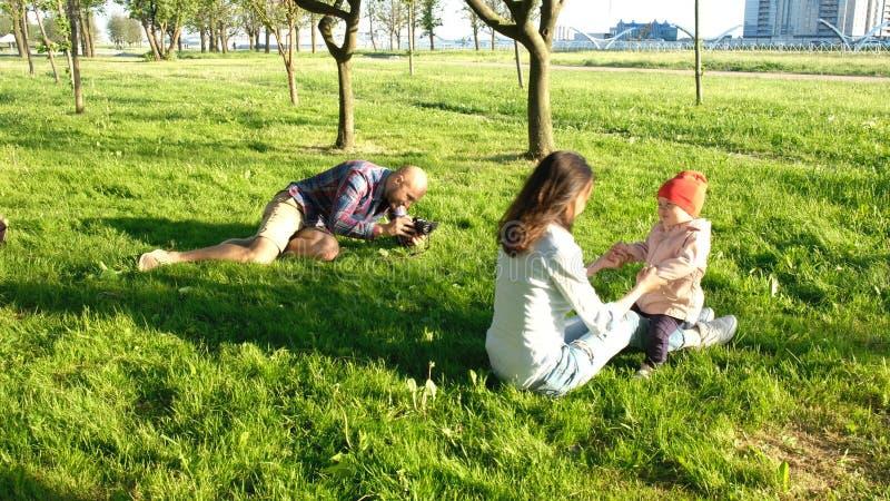 Junger Vater macht ein Foto einer kleinen Tochter mit ihrer Mutter im Park bei Sonnenuntergang Glückliche Familie geht in Natur lizenzfreie stockfotografie