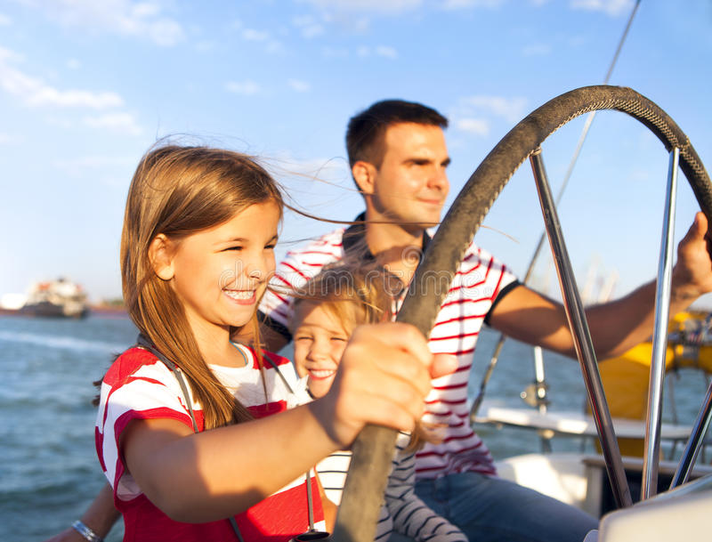 Junger Vater mit entzückenden Töchtern auf einem großen Boot stockfotografie