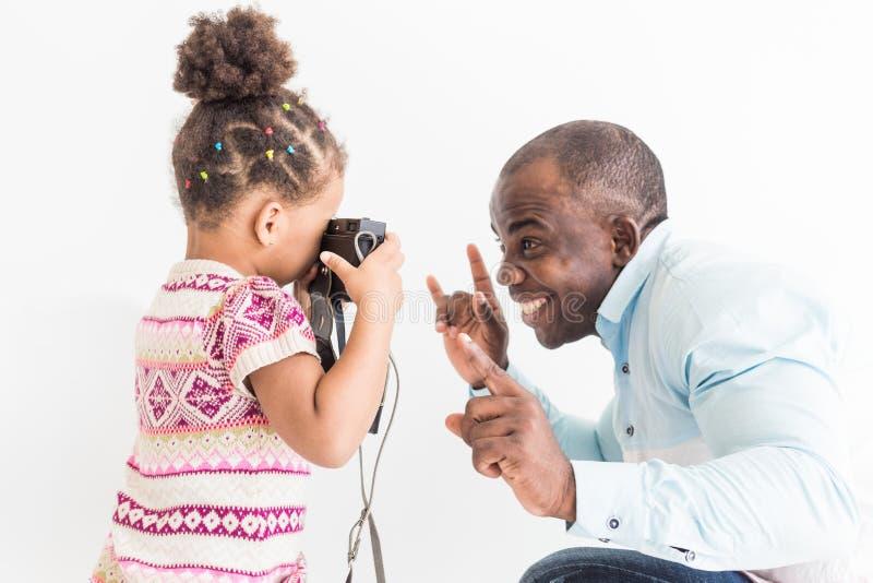 Junger Vater mit seiner netten kleinen Tochter, die Fotos von einander auf einer alten Weinlesekamera macht stockbild
