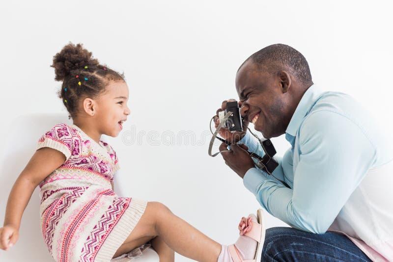 Junger Vater mit seiner netten kleinen Tochter, die Fotos von einander auf einer alten Weinlesekamera macht lizenzfreies stockfoto