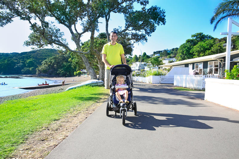 Junger Vater mit seiner netten Kleinkindtochter beim Spaziergängergehen stockfoto