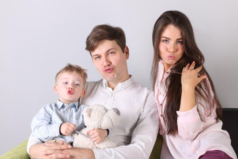 Junger Vater, Mutter, kleine Sohnhaltung mit den Entenlippen stockfoto