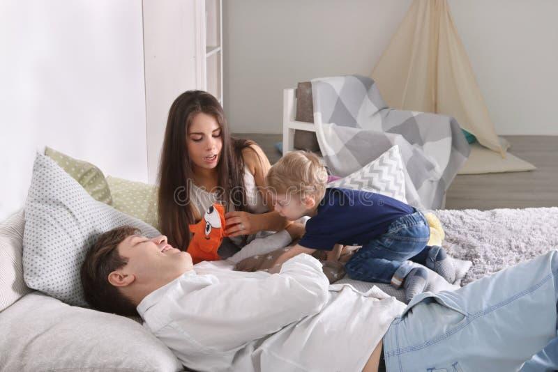 Junger Vater, Mutter, wenig Sohnspiel auf Bett stockfotografie