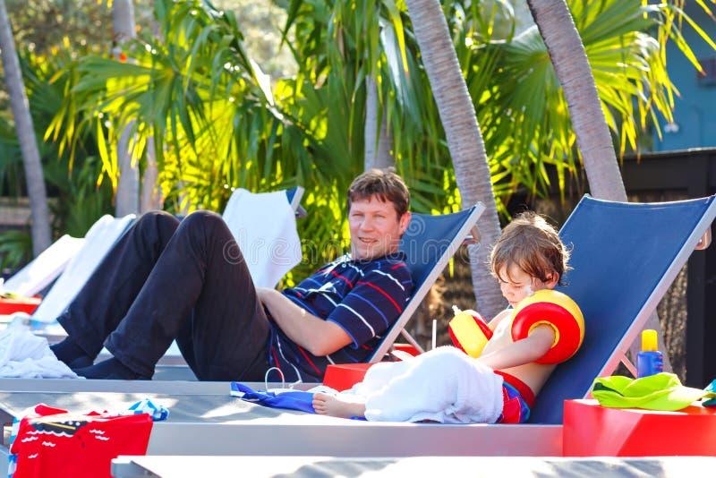 Junger Vater und sein kleiner Sohn, die nahe Swimmingpool stillsteht Mann und kleiner Vorschulkinderjunge bei der Schwimmen float lizenzfreies stockbild