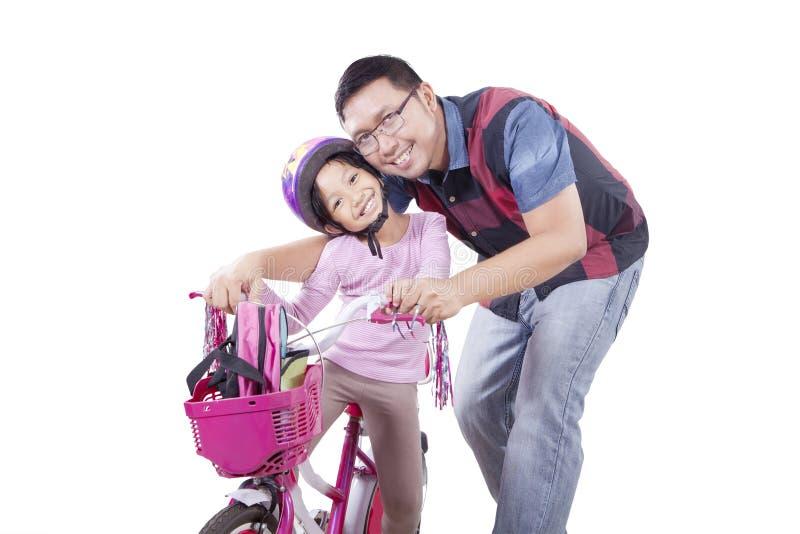 Junger Vater und seine Tochter auf Fahrrad stockfotografie