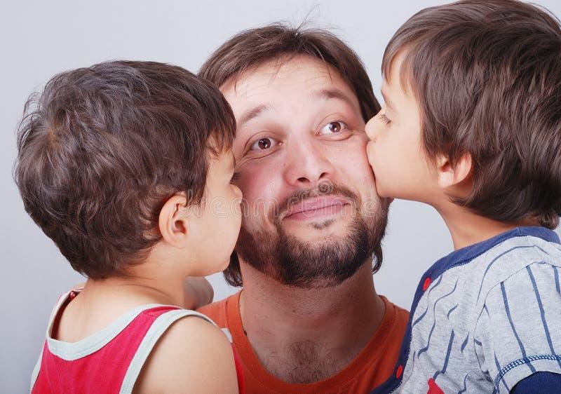 Junger Vater und seine zwei Jungen, die ihn küssen stockfoto
