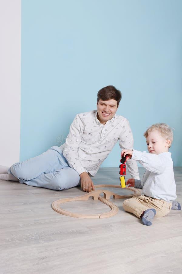 Junger Vater, wenig Sohnspiel mit hölzerner Eisenbahn stockbild