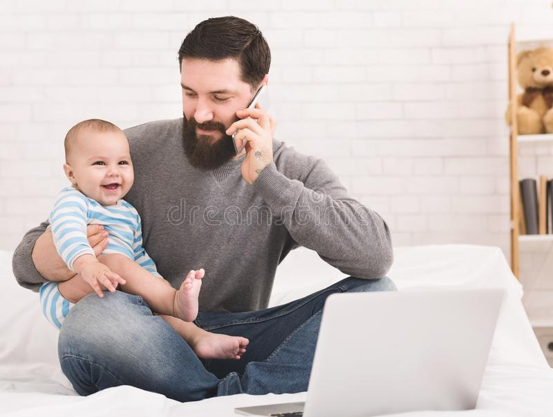 Junger Vati, der zu Hause an Laptop mit seinem Babysohn arbeitet lizenzfreies stockfoto