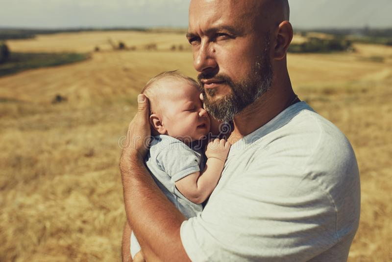 Junger Vati hält ein neugeborenes Baby beim Gehen in Natur glücklicher Vater trägt kurze Hosen und ein T-Shirt Internationaler Va stockbild