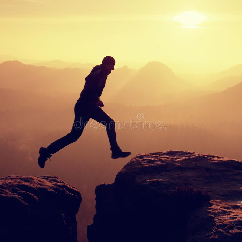 Junger verrückter Mann springen auf Bergspitze Schattenbild des springenden Mannes lizenzfreies stockbild
