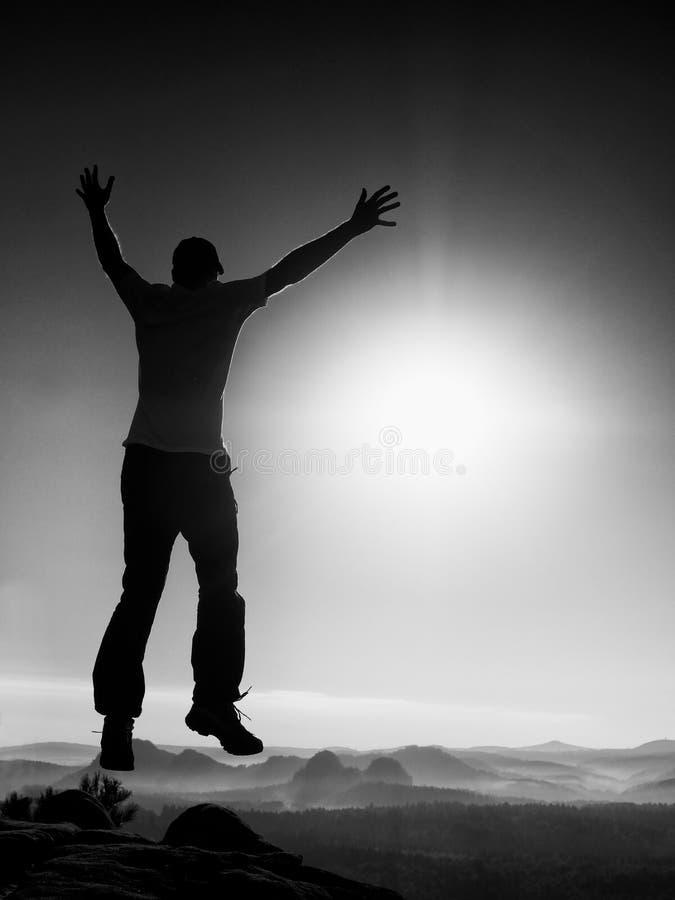 Junger verrückter Mann springt auf Bergspitze Schattenbild des springenden Mannes lizenzfreie stockfotos