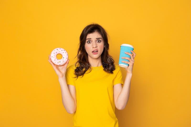 Junger verwirrter M?dchenholdingdonut und -kaffee stockfotografie