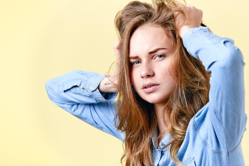 Junger verwirrter Rothaarigejugendlicher mit den Sommersprossen, die ihr Haar ziehen Müde betonte und deprimierte Studentin stockbild